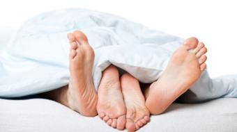 couples feet underblanket bed